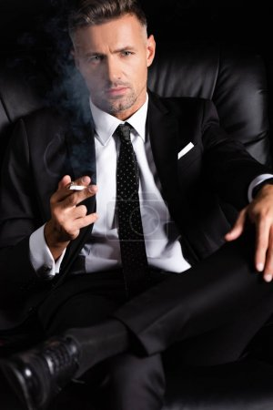 Photo for Confident businessman looking at camera and smoking cigarette on sofa isolated on black - Royalty Free Image