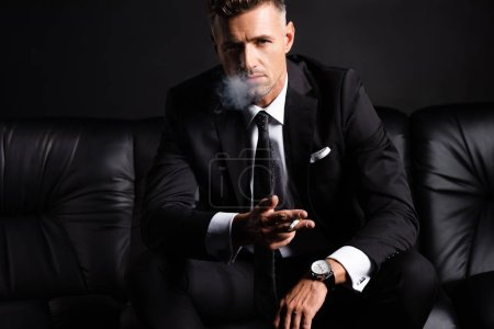 Photo for Handsome businessman smoking cigarette on sofa isolated on black - Royalty Free Image
