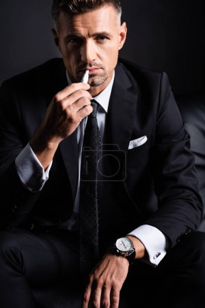 Photo for KYIV, UKRAINE - OCTOBER 11, 2019: Handsome businessman smoking iqos and looking at camera isolated on black - Royalty Free Image