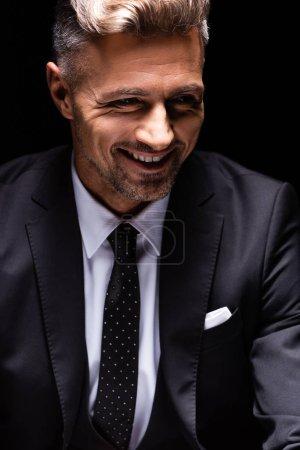 Photo pour Homme d'affaires souriant en costume regardant loin isolé sur noir - image libre de droit