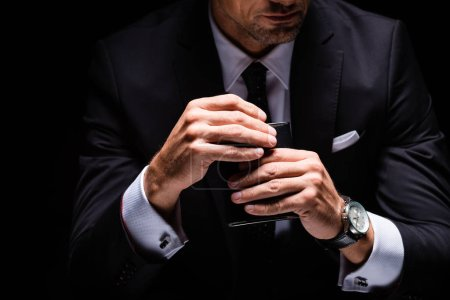 Photo for Cropped view of businessman opening flask isolated on black - Royalty Free Image