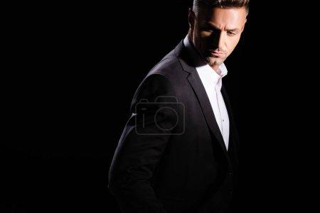 Photo pour Homme d'affaires sérieux regardant vers le bas isolé sur noir - image libre de droit