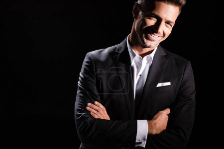 Photo for Smiling businessman with crossed arms looking at camera isolated on black - Royalty Free Image