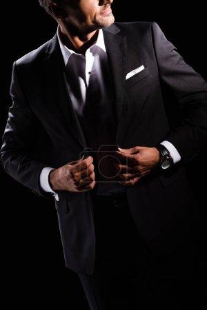 Photo pour Vue recadrée de l'homme d'affaires ajustant les revers de veste isolé sur noir - image libre de droit