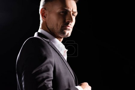 Photo for Side view of confident businessman looking at camera isolated on black - Royalty Free Image