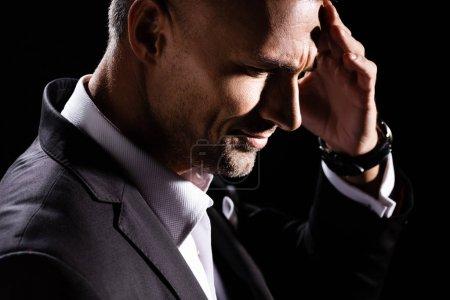 Photo pour Vue latérale de l'homme d'affaires avec la main par la tête isolé sur noir - image libre de droit