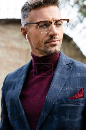 Photo for Handsome businessman in wireless earphones looking away outdoors - Royalty Free Image