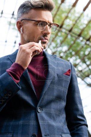 Photo pour Vue à faible angle de l'homme d'affaires dans les écouteurs sans fil fumant une cigarette électronique à l'extérieur - image libre de droit