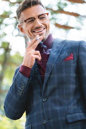Photo pour Beau homme d'affaires fumant la cigarette tout en souriant à l'extérieur - image libre de droit