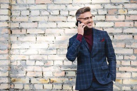 Photo pour Homme d'affaires souriant parlant sur smartphone avec mur de briques en arrière-plan - image libre de droit