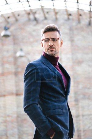 Photo pour Vue latérale de bel homme d'affaires regardant loin sur la rue urbaine - image libre de droit