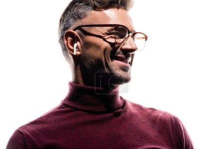 Foto de Hombre sonriente con auriculares inalámbricos y anteojos mirando hacia otro lado aislado en blanco - Imagen libre de derechos