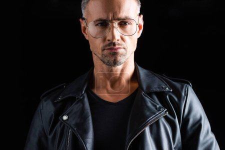 Photo pour Homme élégant confiant en lunettes de soleil et veste en cuir regardant la caméra isolée sur noir - image libre de droit