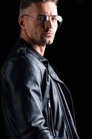 Photo for Side view of handsome man in leather jacket looking at camera isolated on black - Royalty Free Image