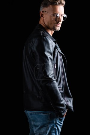 Photo for Side view of handsome man in leather jacket and sunglasses looking away isolated on black - Royalty Free Image
