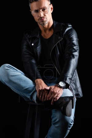 Photo for Confident man in biker jacket and jeans looking at camera while sitting on chair isolated on black - Royalty Free Image