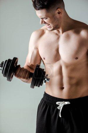 Photo pour Bodybuilder musclé sexy avec torse nu exercice avec haltère isolé sur gris - image libre de droit