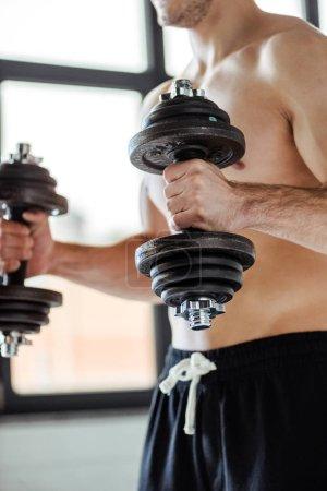 Photo pour Vue partielle de bodybuilder musculaire sexy avec torse nu exercice avec haltères - image libre de droit
