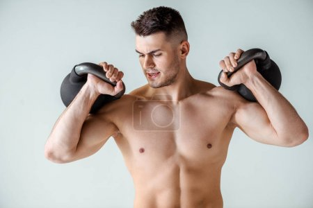 Photo pour Sexy muscular bodybuilder with bare torso exercise with kettlebells isolated on grey - image libre de droit
