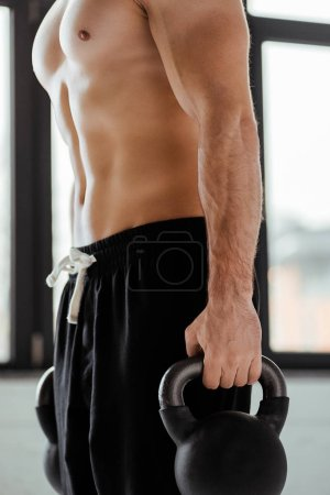 partial view of sexy muscular bodybuilder with bare torso exercising with kettlebells