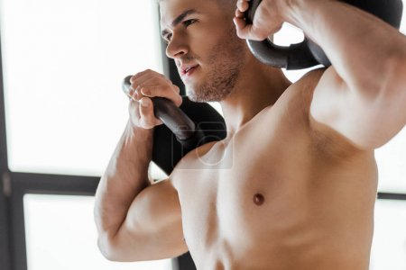 Photo for Sexy muscular bodybuilder with bare torso exercising with kettlebells - Royalty Free Image