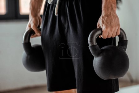 Photo for Partial view of bodybuilder holding kettlebells - Royalty Free Image