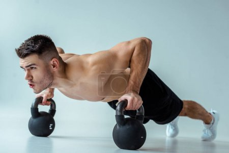 Photo for Sexy muscular bodybuilder with bare torso doing push ups with kettlebells on grey - Royalty Free Image