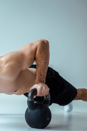 Photo for Partial view of sexy muscular bodybuilder with bare torso doing push ups with kettlebell on grey - Royalty Free Image