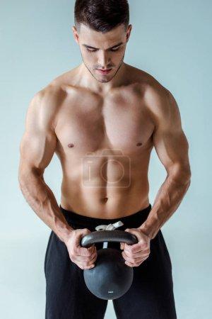 Photo pour Musclé bodybuilder sexy avec torse nu exercice avec kettlebell isolé sur gris - image libre de droit
