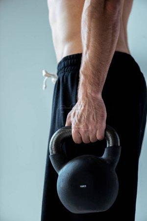 Photo pour Vue partielle du bodybuilder musclé sexy faisant de l'exercice avec kettlebell isolé sur gris - image libre de droit