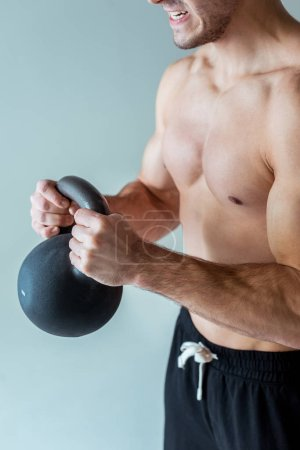 Photo for Partial view of sexy muscular bodybuilder with bare torso exercising with kettlebell isolated on grey - Royalty Free Image
