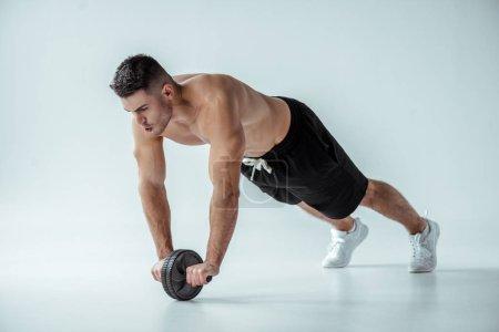 Photo pour Bodybuilder musclé sexy avec torse nu exercice avec roue ab sur fond gris - image libre de droit