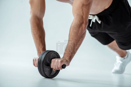 Photo for Cropped view of sexy muscular bodybuilder with bare torso exercising with ab wheel on grey background - Royalty Free Image