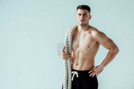 Photo pour Bodybuilder musclé sexy avec torse nu posant avec corde de combat isolé sur gris - image libre de droit
