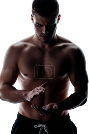 Photo for Sexy muscular bodybuilder with bare torso applying talcum powder on hands isolated on white - Royalty Free Image