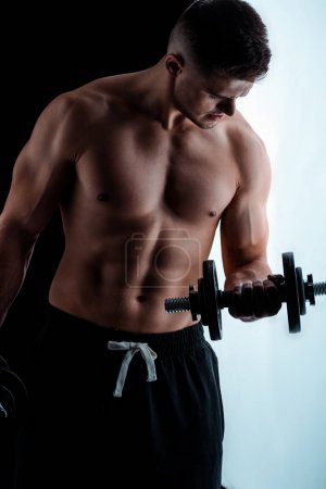 Photo for Sexy muscular bodybuilder with bare torso exercising with dumbbell - Royalty Free Image