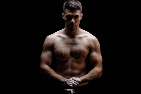 Photo for Sexy muscular bodybuilder with bare torso with talcum powder on hands isolated on black - Royalty Free Image