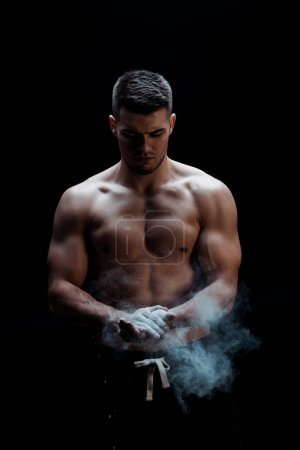 Photo for Sexy muscular bodybuilder with bare torso applying talcum powder on hands on black background with smoke - Royalty Free Image