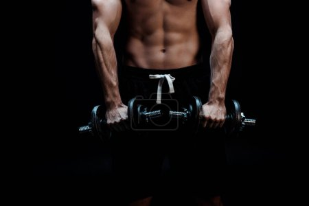 Photo for Partial view of sexy muscular bodybuilder with bare torso excising with dumbbells isolated on black - Royalty Free Image