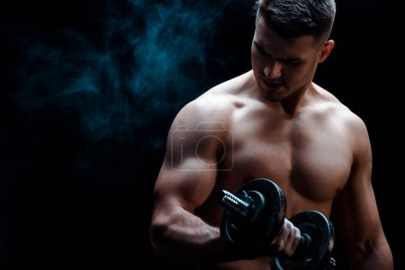 Photo for Sexy muscular bodybuilder with bare torso excising with dumbbell on black with smoke - Royalty Free Image