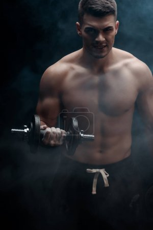 Photo pour Sexy muscular bodybuilder with bare torso excising with halmbell on black background with smoke - image libre de droit