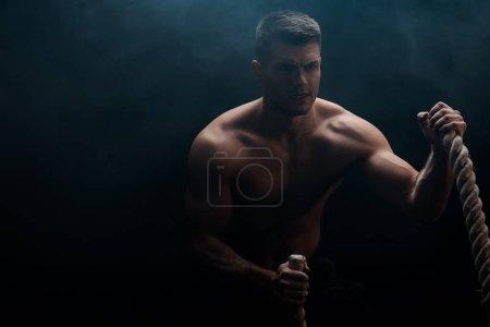 Foto de Sexta carrocería muscular con torso desnudo excitante con cuerda de batalla sobre fondo negro con humo. - Imagen libre de derechos