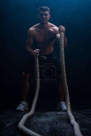 Photo pour Foyer sélectif de bodybuilder musclé sexy avec torse nu excitant avec corde de combat sur fond noir avec de la fumée - image libre de droit