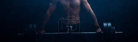 Photo for Cropped view of sexy muscular bodybuilder with bare torso excising with barbell on black background with smoke, panoramic shot - Royalty Free Image