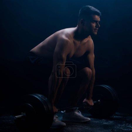 Foto de Sexta carrocería muscular con torso desnudo excitante con campana en fondo negro con humo. - Imagen libre de derechos