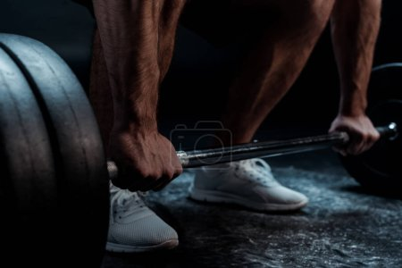 Photo for Cropped view of muscular bodybuilder excising with barbell on black background - Royalty Free Image