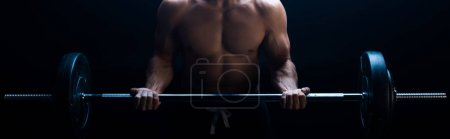 Photo for Partial view of sexy muscular bodybuilder with bare torso excising with barbell isolated on black, panoramic shot - Royalty Free Image