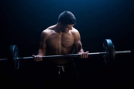 sexy muscular bodybuilder with bare torso excising with barbell on black background with smoke