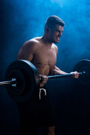 tense muscular bodybuilder with bare torso excising with barbell on black background with smoke