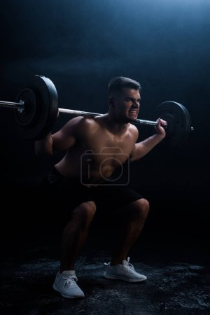 tense sexy muscular bodybuilder with bare torso squatting with barbell on black background